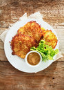 Potato fritters fried to a golden crispness overhead view of delicious served with fresh leafy green lettuce and mustard Royalty Free Stock Photos