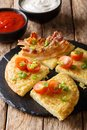 Potato pancakes with bacon, tomatoes, onions and sauces close-up Royalty Free Stock Photo