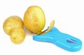 Potato peeler and potatoes Stock Photo
