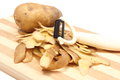 Potato with peels and peeler lying on wooden cutting board heap of whole Stock Image