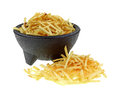 Potato sticks front and in bowl a group of of a full black pedestal Royalty Free Stock Photography