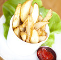 Potato wedges on plate served with ketchup Royalty Free Stock Images
