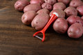 Potatoes with peeler Royalty Free Stock Photo