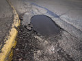 Pothole large deep as an example of poor road maintenance due to cutbacks on the infrastructure budget Royalty Free Stock Photo