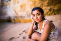 Potrait latin girl sitting on golden sand at beach near rocks and looking at ocean.  Summer vocation Royalty Free Stock Photo