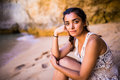 Potrait maxican girl sitting on golden sand at beach near rocks and looking at ocean.  Summer vocation Royalty Free Stock Photo