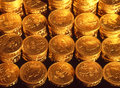 Pound coins stacked in organised regular rows under tungsten lighting to give a golden hue Stock Photo