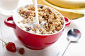 Pour milk into the bowl for healthy breakfast with muesli and fruit Stock Image