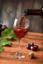 Pour red wine into the glass - wood background Royalty Free Stock Photo