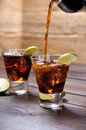 Pour the rum and cola cuba libre with lime, ice Royalty Free Stock Photo