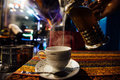 Pour tea into a cup at an Street cafe. Jets of steam. Arabic flavor Royalty Free Stock Photo