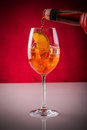 Pouring aperitif in a glass over ice cubes and orange slice