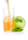 Pouring apple juice into a glass, green apples Stock Image