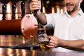 Pouring beer cropped image of smiley bartender poring to the mug Royalty Free Stock Photography