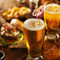 Pouring beer into glass with burgers on wooden table top Stock Photo