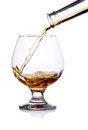 Pouring from bottle of cognac in glass isolated Stock Image