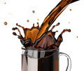Pouring coffee splashing into a glass mug at white background Royalty Free Stock Photo