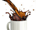 Pouring coffee splashing into a glass mug at white background Stock Photos