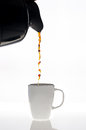 Pouring coffee in to cup on white background Stock Photos