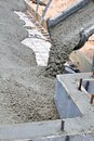 Pouring concrete slab wet cement pours down a truck chute to fill a at a home building construction site Royalty Free Stock Photo