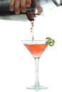 Pouring a cosmo male hands vodka cocktail in to chilled martini glass with llime garnish Stock Photos