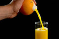 Pouring fresh orange juice directly from an orange into a glass in front of black background Royalty Free Stock Photos