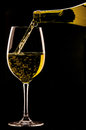 Pouring a glass of wine on black background. Royalty Free Stock Photo