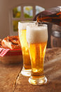 Pouring glasses of frothy beer Stock Photography