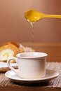 Pouring honey into tea mug and croissant in the background Stock Images
