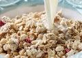 Pouring milk into bowl of muesli Royalty Free Stock Photo