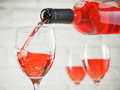 Pouring pink wine from bottle into wineglass Royalty Free Stock Photo