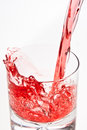 Pouring a red beverage making an mixed drink with by it into glass juice splash isolated on white Royalty Free Stock Image
