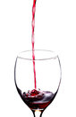 Pouring red wine on a empty glass over a white background Royalty Free Stock Photos