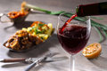 Pouring red wine and food Royalty Free Stock Photo