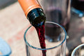 Pouring red wine into glass stream from bottle to Royalty Free Stock Photos