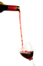 Pouring red wine shaped as a heart from a bottle into a glass Royalty Free Stock Photo