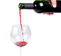 Pouring red wine into a wineglass hand from an unlabelled bottle isolated on white Stock Photography
