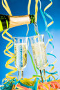 Pouring sparkling wine a bottle and two glass of streamers and blue background Royalty Free Stock Photo