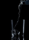 Pouring water on a glass on black background Royalty Free Stock Photo