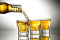 Pouring whiskey into shot glasses Stock Photography