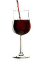 Pouring wine red into a glass isolated on a white background Royalty Free Stock Photography