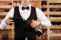 Pouring wine to decanter cropped image of confident young sommelier standing in front of shelf and the Royalty Free Stock Photos