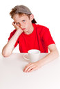 Pouting child behind white cup Royalty Free Stock Photo