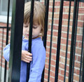 Pouting child a three year old girl pouts while looking out from a fence Stock Photography