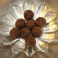 Powdered chocolate truffles organic round caramel in a flower like glass dish placed inside a stainless steel bowl Stock Image