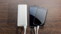 Power Bank charging two smartphones - dark wooden background
