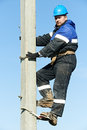 Power electrician lineman at work on pole repairman worker climbing electric post Stock Photography