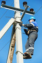 Power electrician lineman at work on pole repairman worker climbing electric post Royalty Free Stock Photos