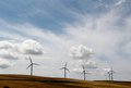 Power generating wind turbines dramatic sky a field of in the hills of sicily in slight backlight landscape cut Royalty Free Stock Photography