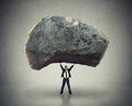 Power leadership ability to inspire man lifting up huge boulder of with the as a businessman a removing a large obstacle and Royalty Free Stock Photo